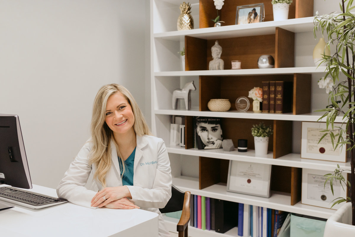 dentist at her desk with bookshelf