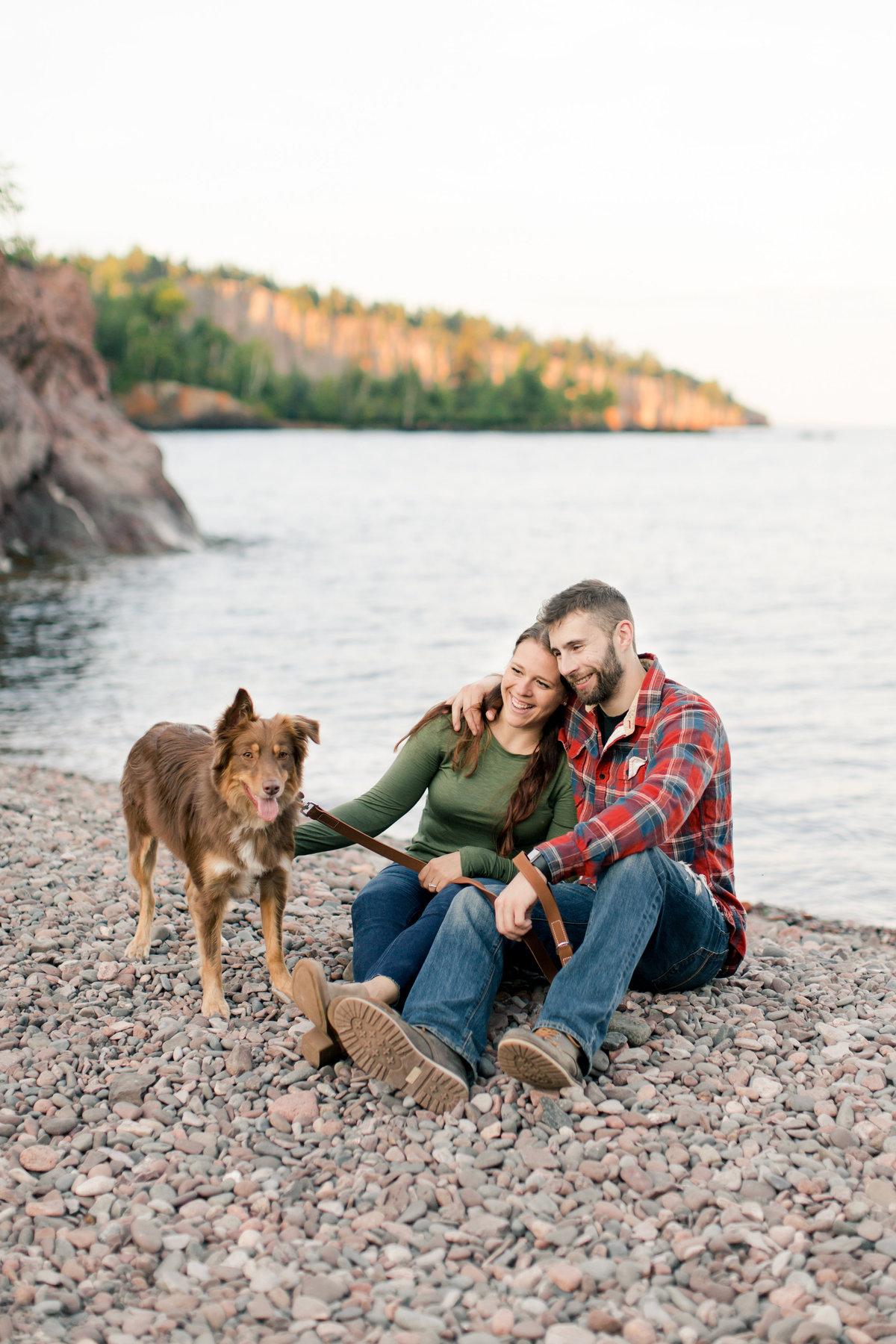 dog and couple on the pebble beach of minnesota north shore state park with lake superior in the backgrond