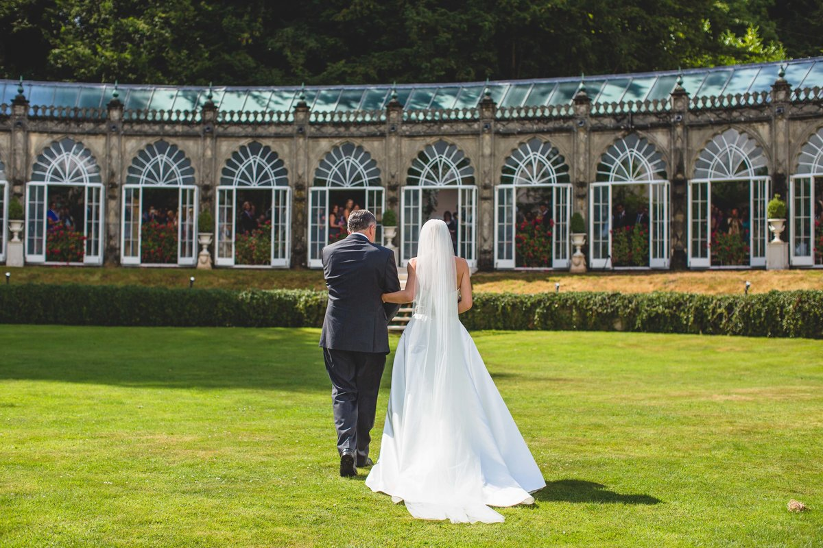 the bride walking down the aisle in outdoor wedding ceremony at sezincote house