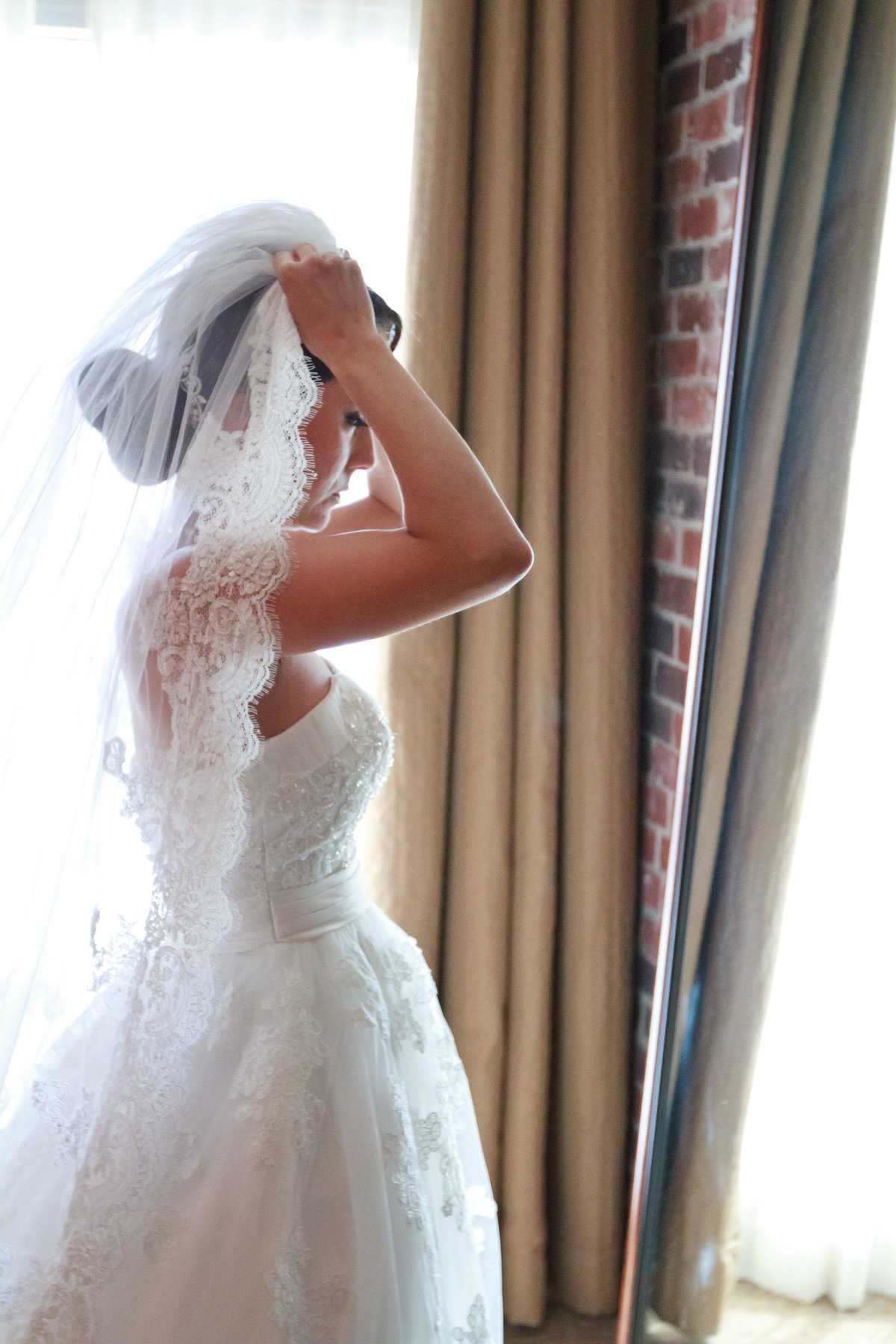 Bride putting on her veil getting ready at the Hotel Contessa for her same sex wedding in downtown San Antonio