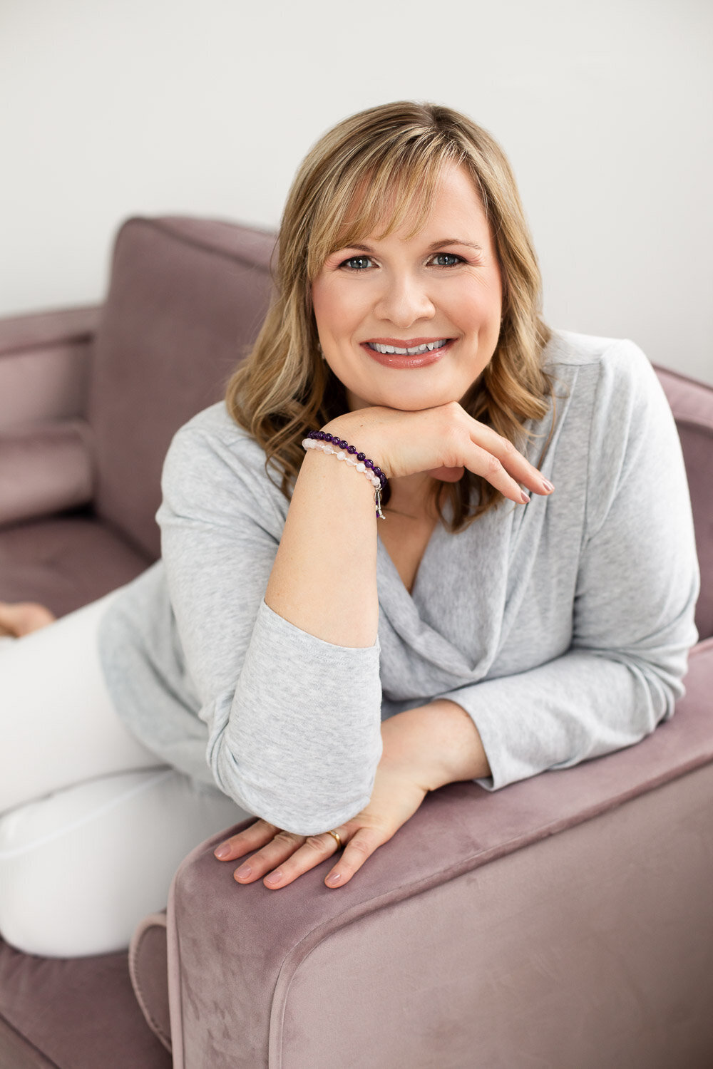 Woman sitting on pink sofa smiling
