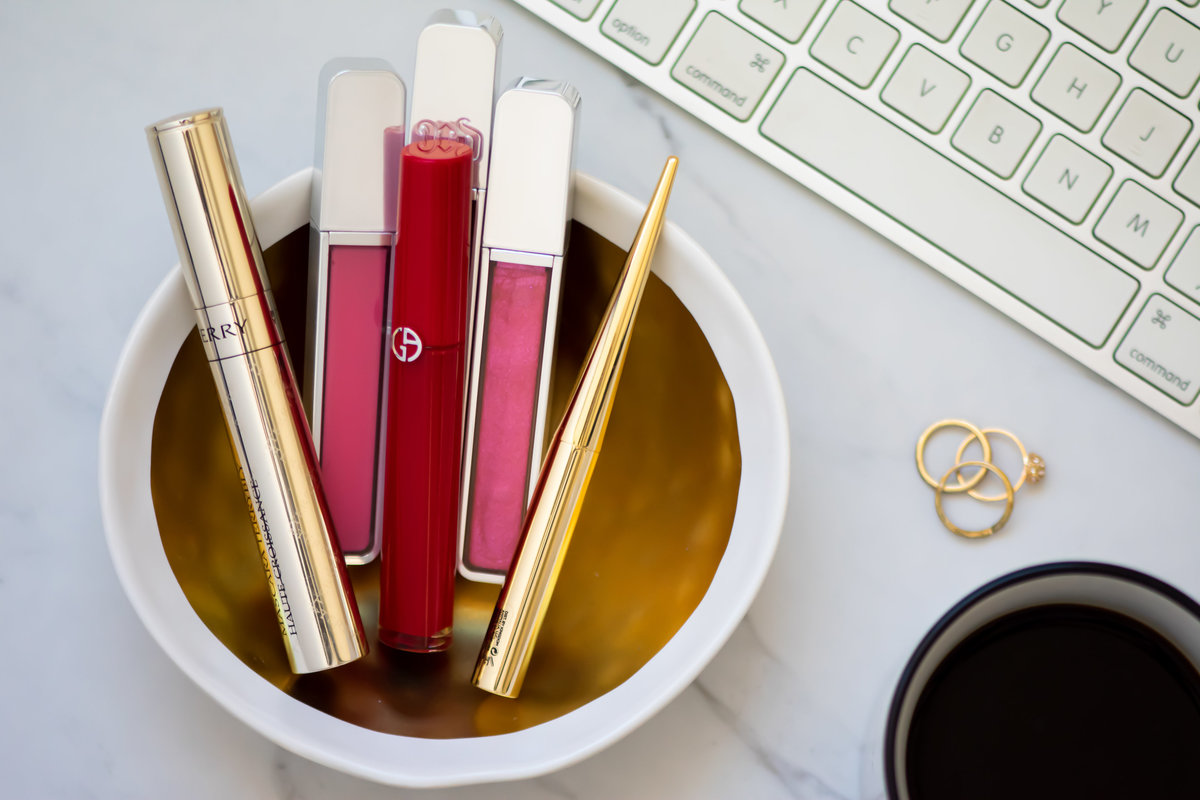 Bowl of expensive lip sticks and lip glosses on desk with rings, cup of coffee, and keyboard
