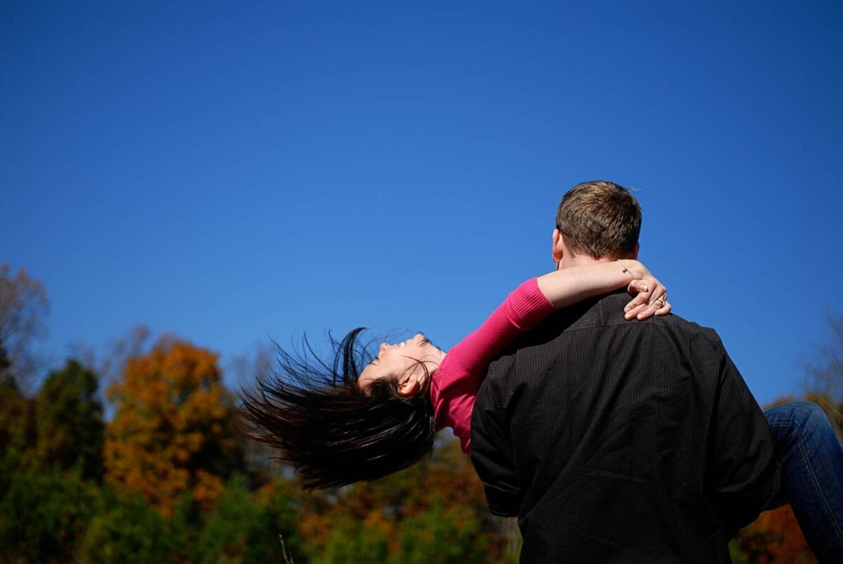 a man spins a woman around in the air in front of clear blue skies as her hair flys