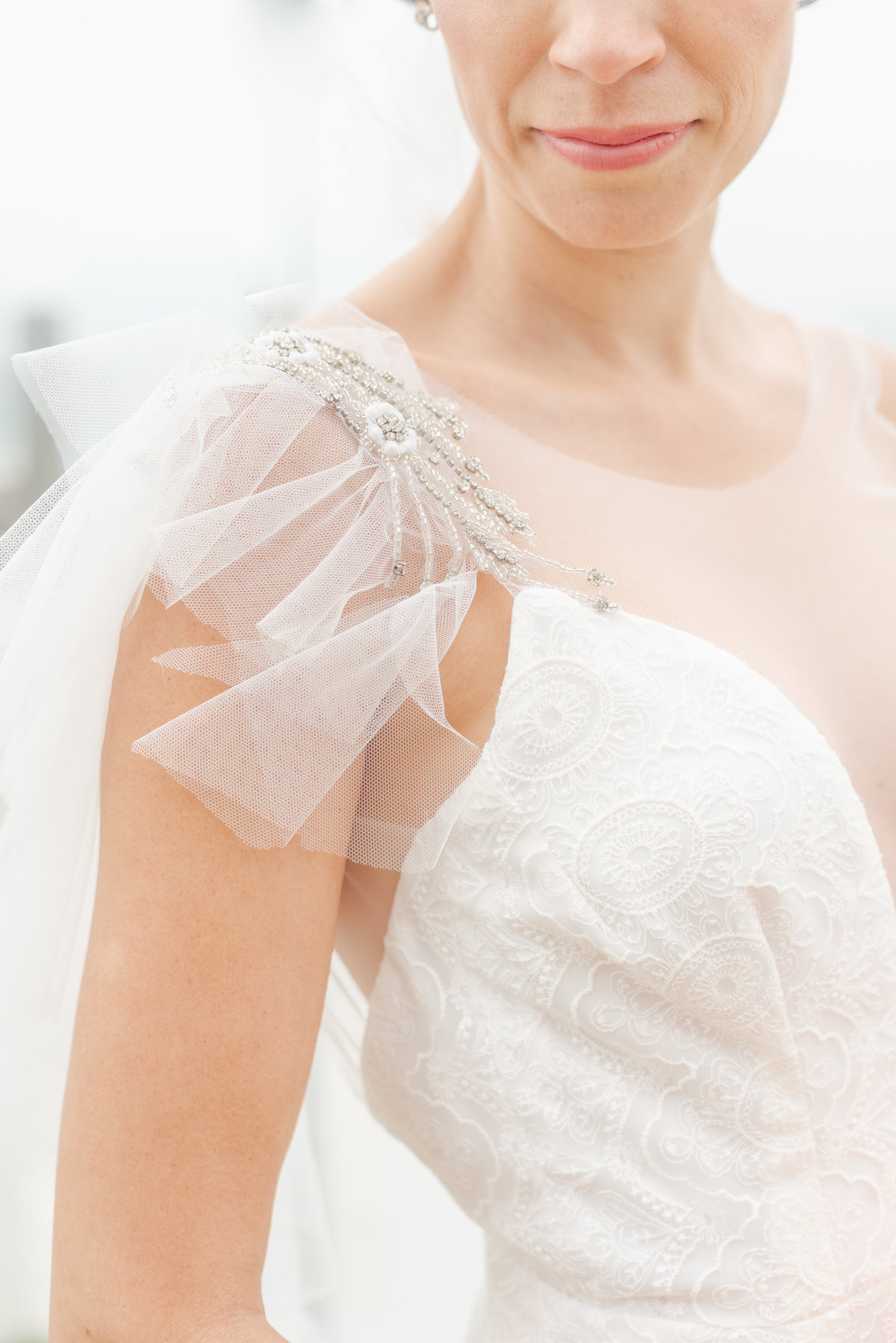 Tulle sleeves and delicate beading make up the shoulder of a wedding dress during wedding at Offshore Chicago