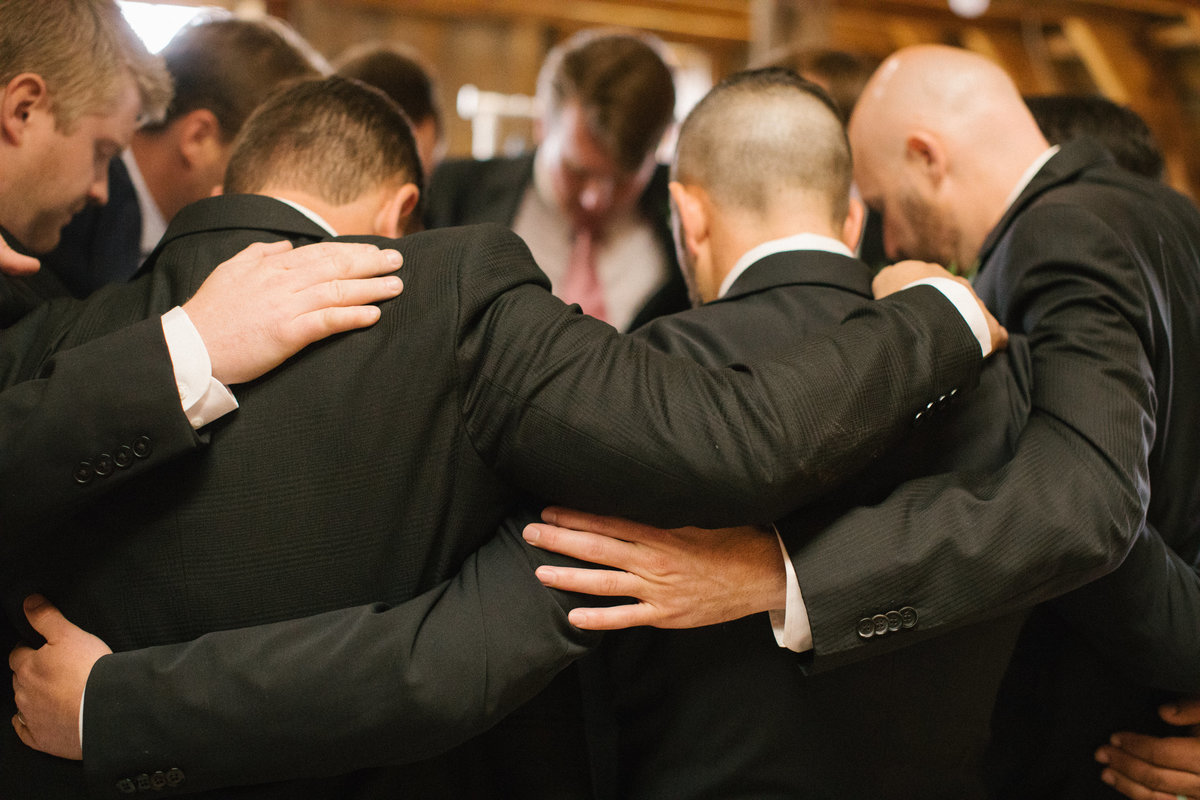 A group of men praying together.