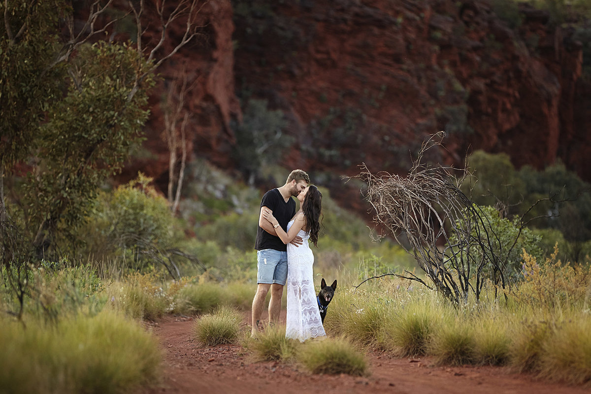 Couple kissing in natural rock location with dog hiding behind them