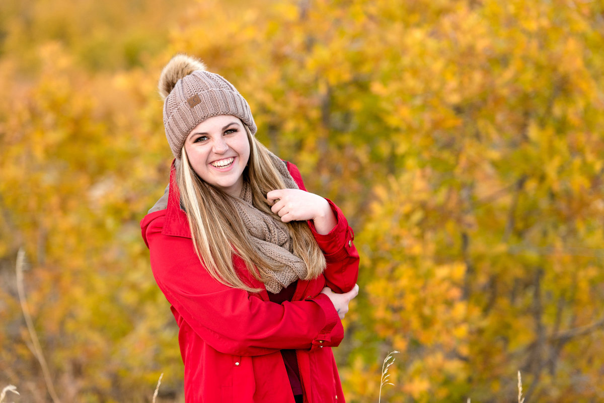 senior girl smiles at the camera during the fall at snowbasin