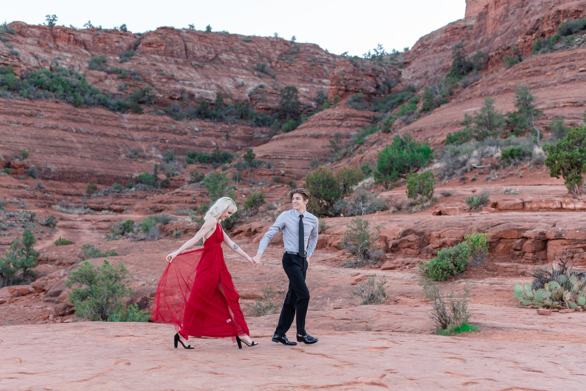 groom leads bride in red dress in sedona arizona