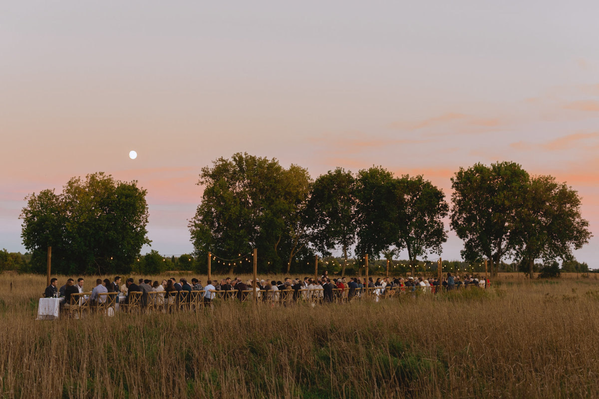long harvest table wedding reception in  field at sunset