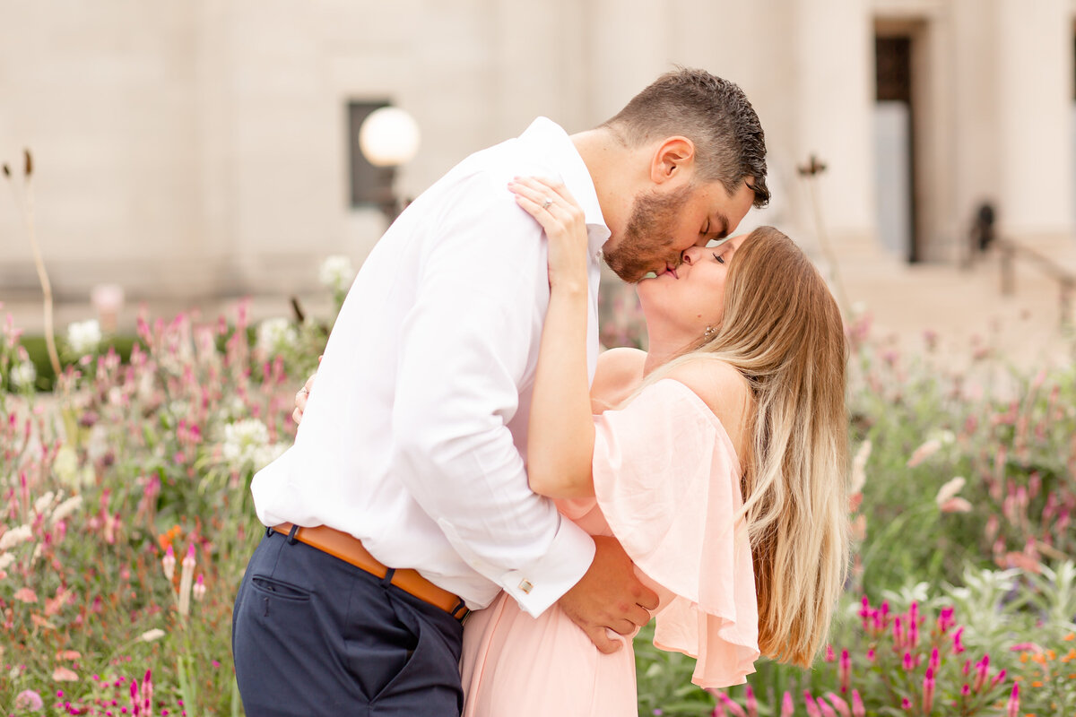 Summer Sunset Engagement Session with pink off the shoulder dress couple kissing by wildflowers at St. Louis Art Museum in Forest Park in St. Louis by Amy Britton Photography Photographer in St. Louis
