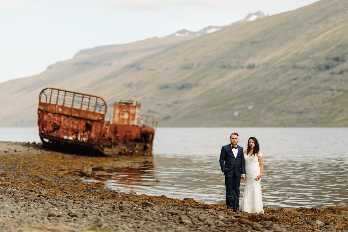 Bride & groom pose in front of an abandoned ship in an Iceland Fjord after their Iceland wedding.