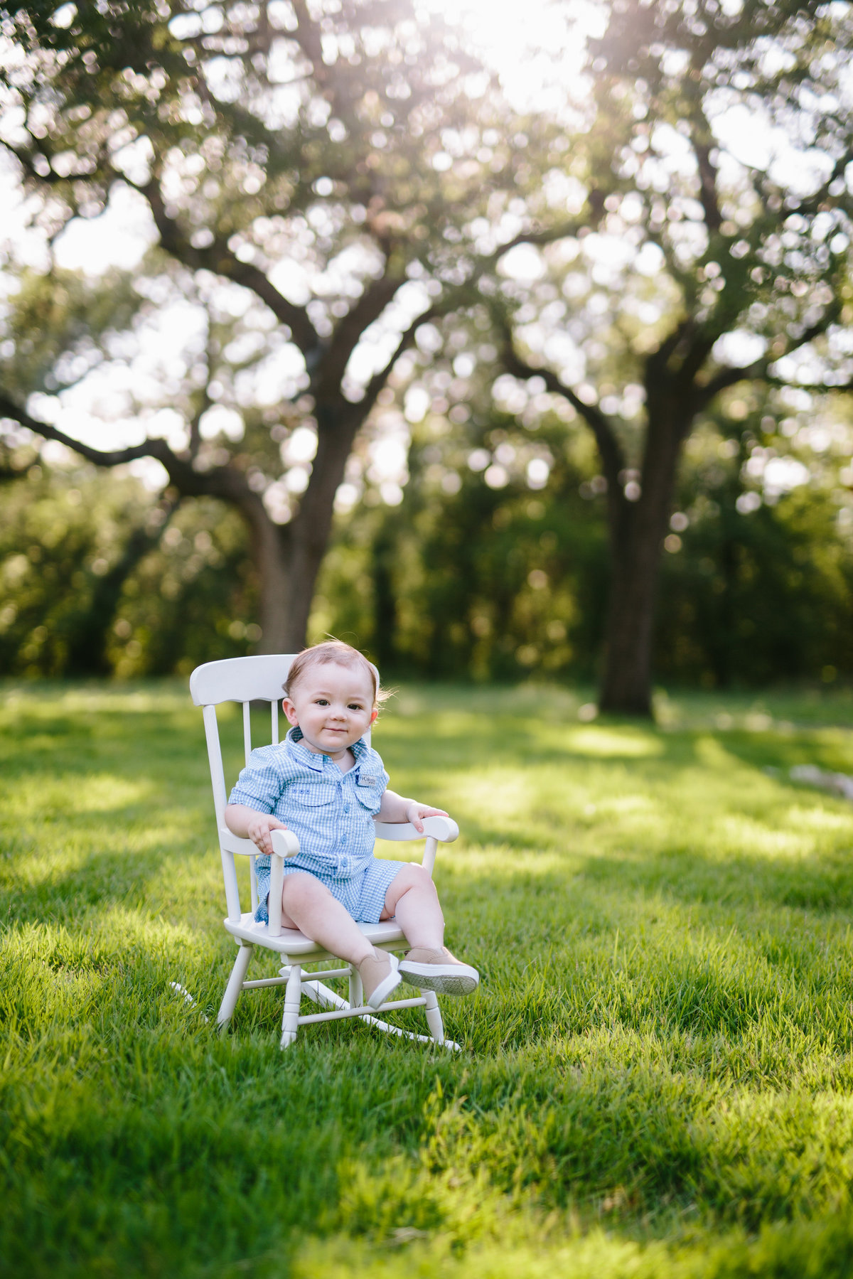 Photo of Baby toddler sitting in white rocking chair wearing blue jumper in forrest clearing at private San Antonio residence
