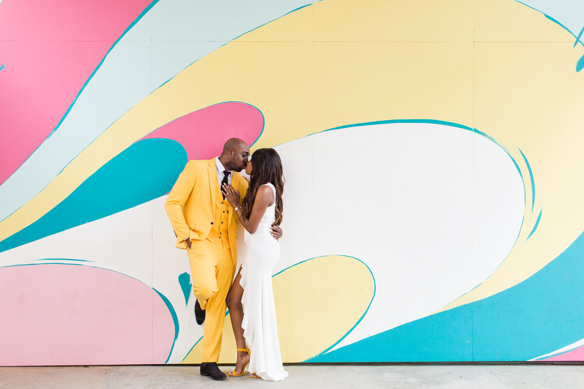 engaged couple standing by graffiti wall at ponce city market