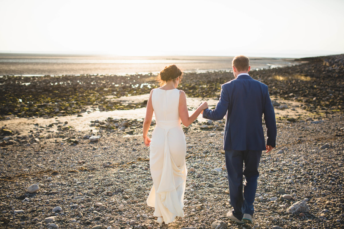 wedding couple walking on the stoney beach holding hands