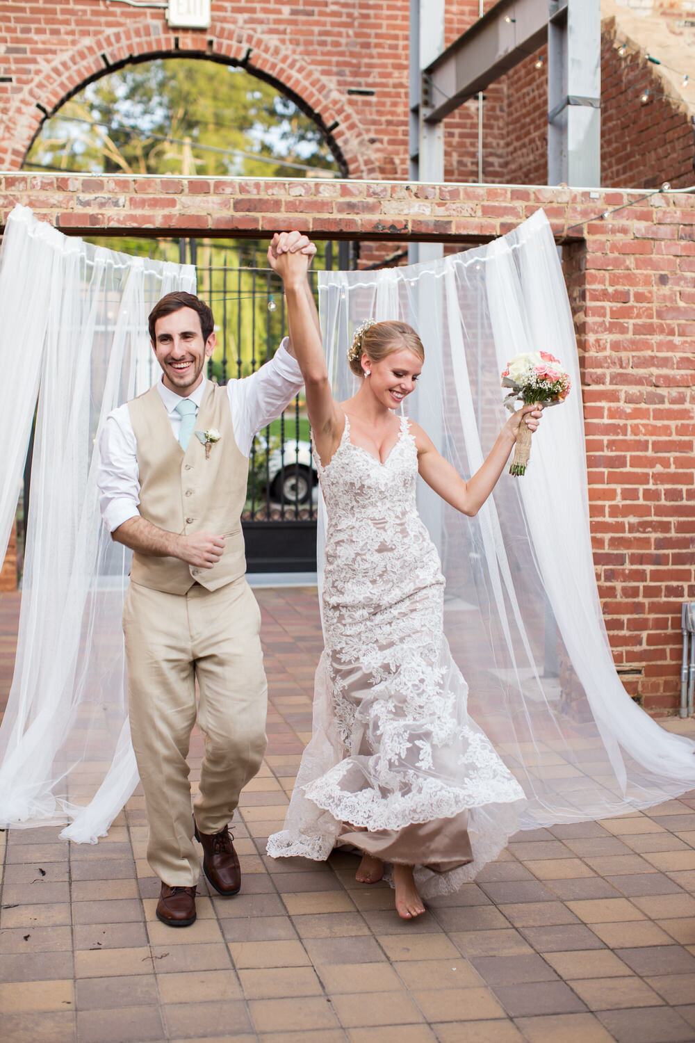 happy bride and groom walking into outdoor reception