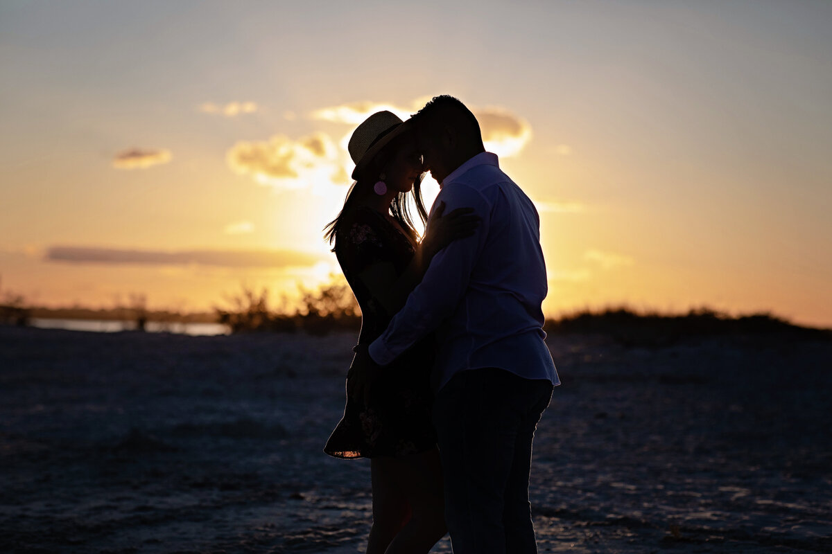 An image of a couple marking their engagement as they are silhouetted against a golden sky with the sun setting behind them as they hold each other close and tenderly touch foreheads by Garry & Stacy Photography Co - Clearwater engagement photographer