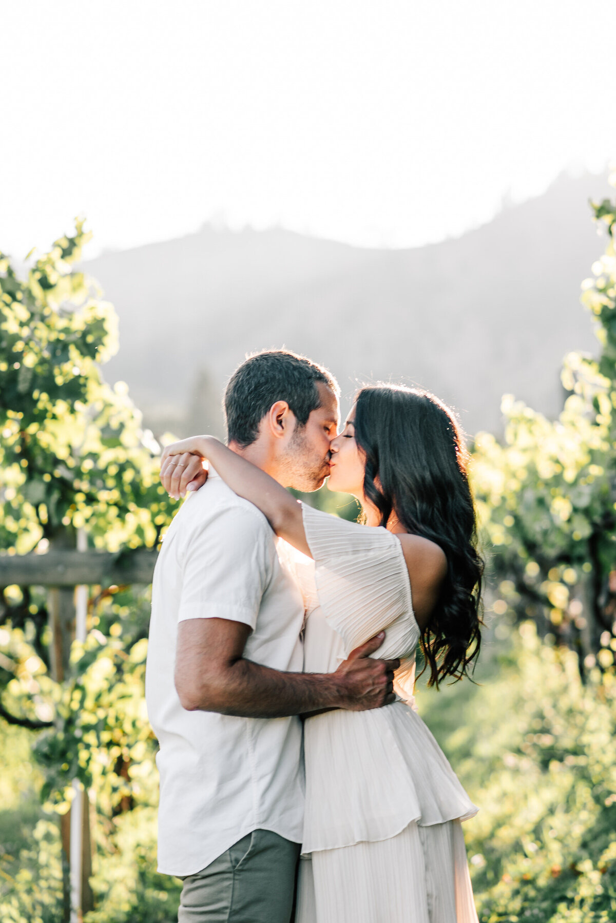 Couple kissing in the vineyard during engagement session at Beecher Hill House