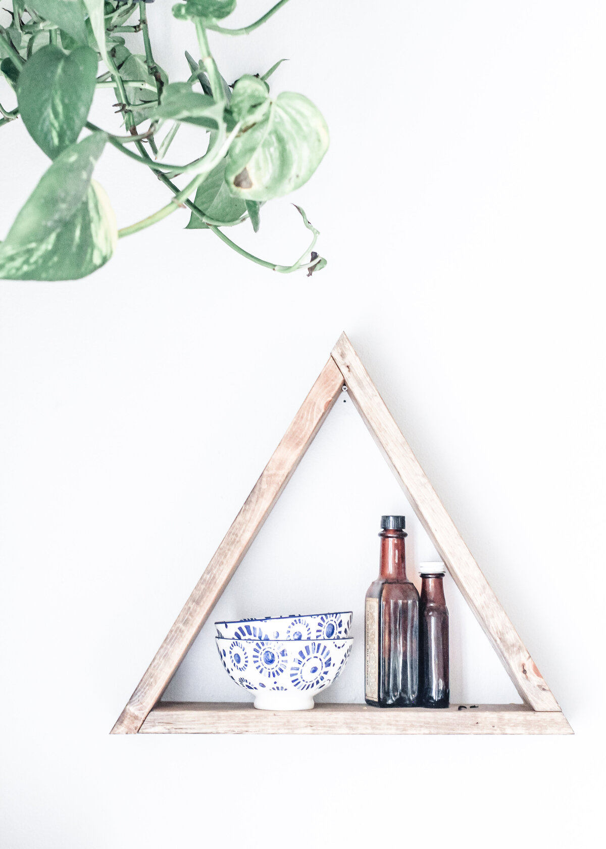 A close up image of a wooden triangle shelf with an ornate bowl and amber bottle.