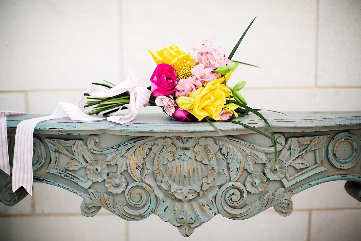 A vintage mantel with a colorful bouquet on top.