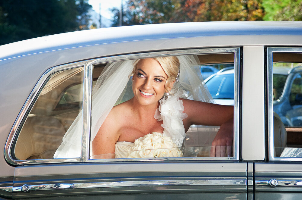 blonde bride looking out the window of her vintage Rolls Royce wedding car in Kerry