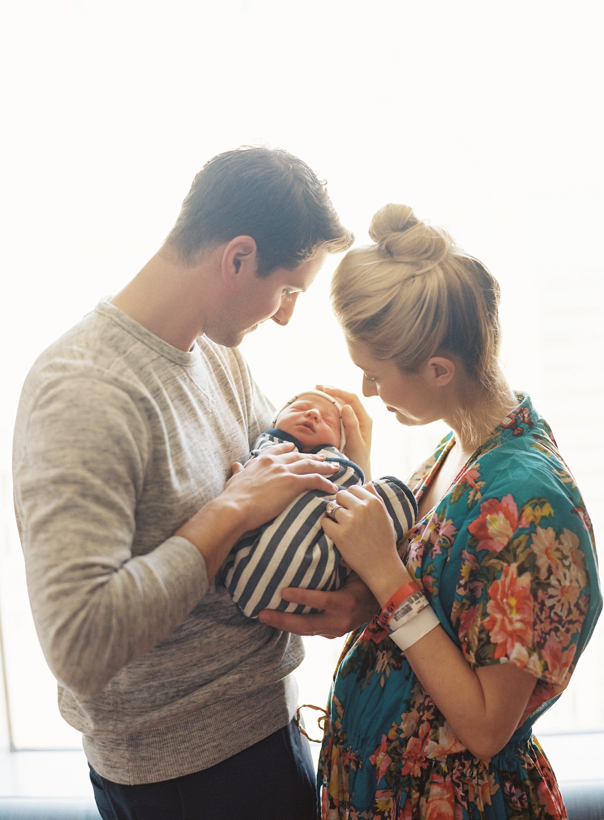 mom and dad with newborn baby at hospital