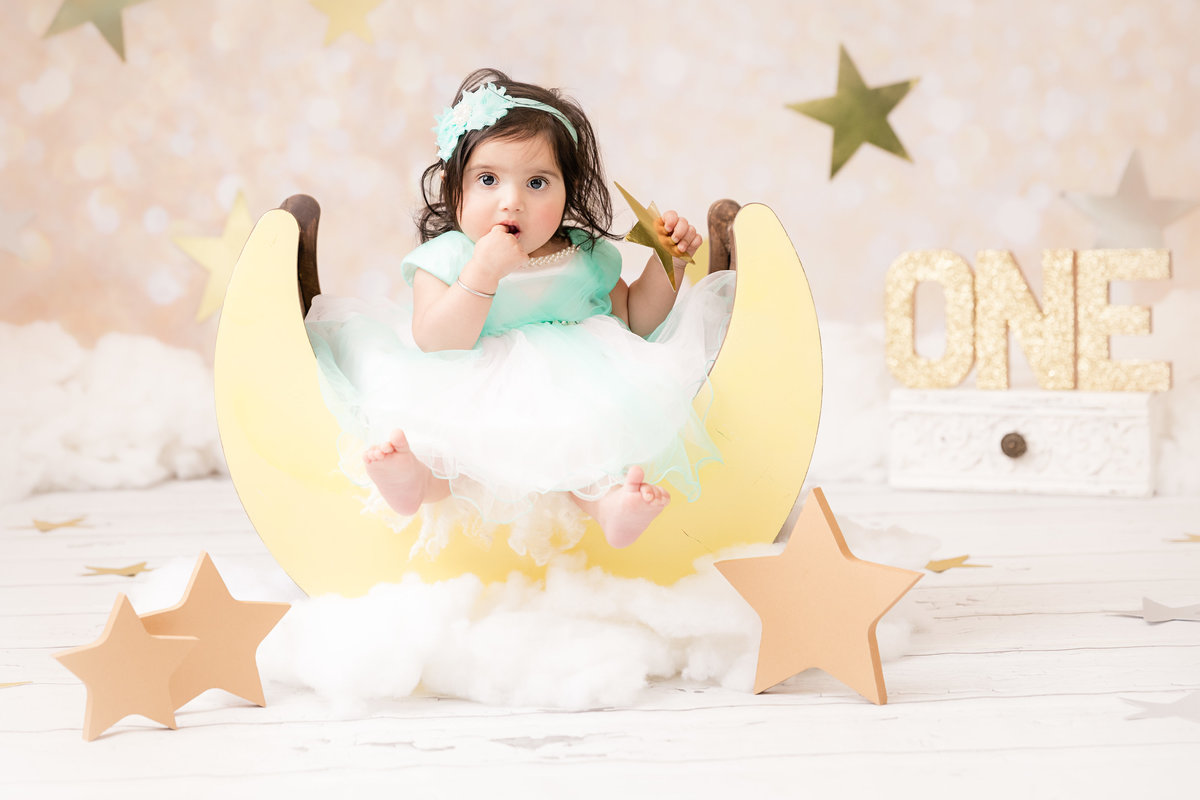 Little girl sitting on the moon for her first birthday