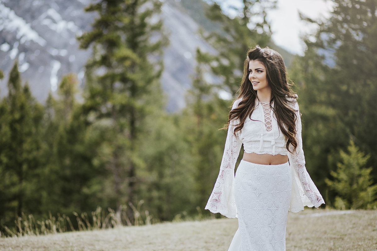 Bride on top of mountain wearing a Delica Bridal dress by Daughter's of Simone