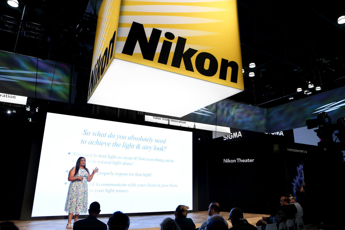Photographer Kiamarie Stone on stage speaking at photography conference for Nikon