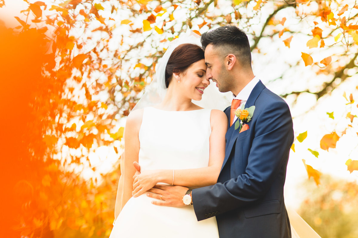 bride and groom with autumn colours for background