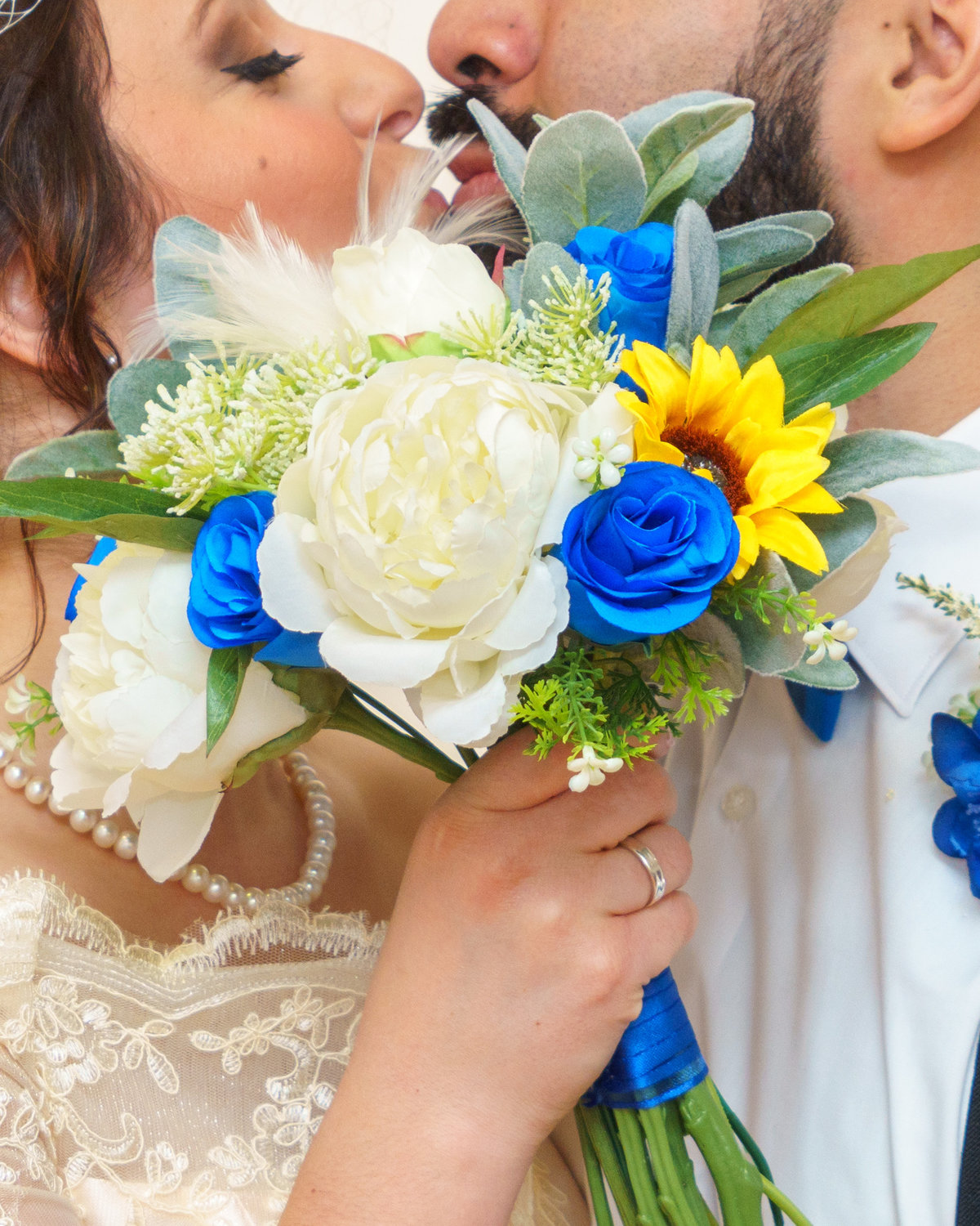 Bride & Groom kissing and using bouquet to hide