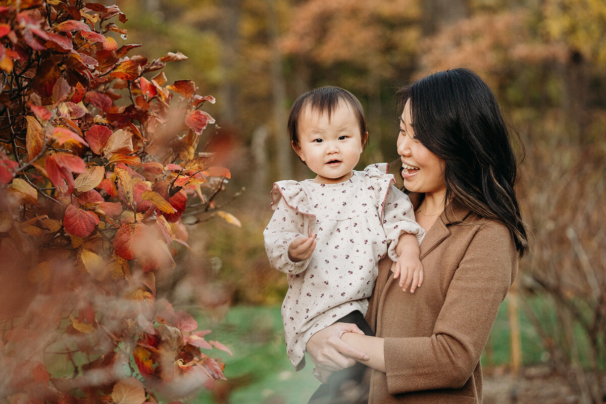 mother holds toddler daughter by autumn leaves