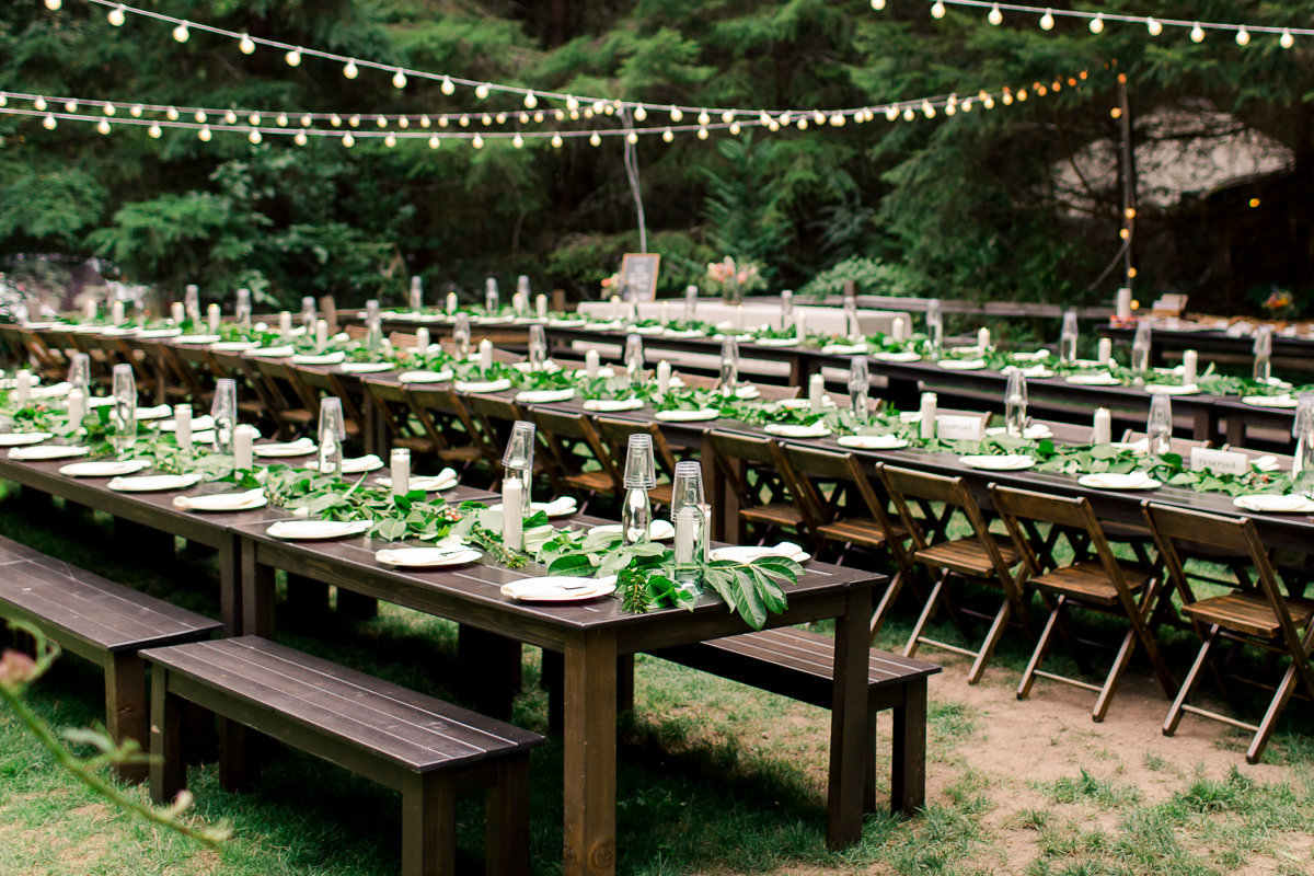 outdoor reception setup under cafe lights with wood tables and benches