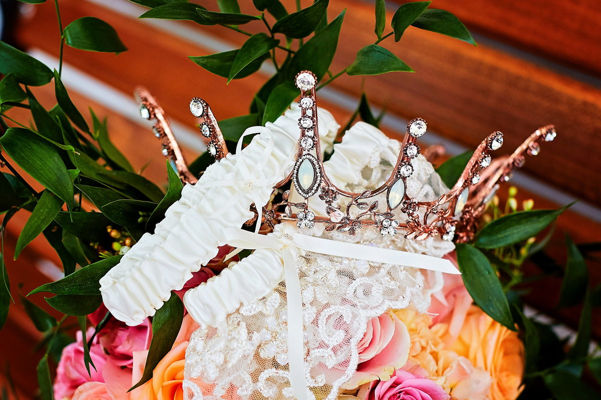 Detail of offbeat bride's colorful pink bouquet, rose gold crown, and garter in Beaufort, SC