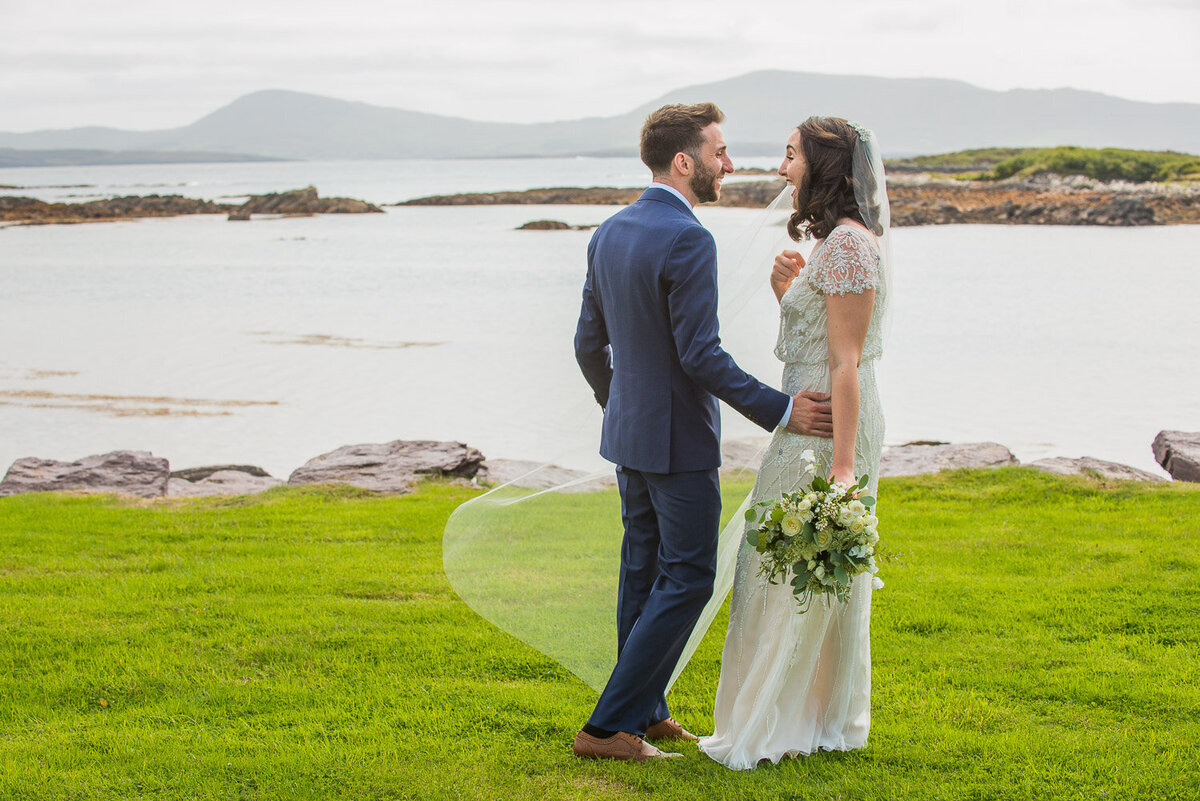 bride and groom at the first look, standing on the grass overlooking Castlecove beach in Kerry