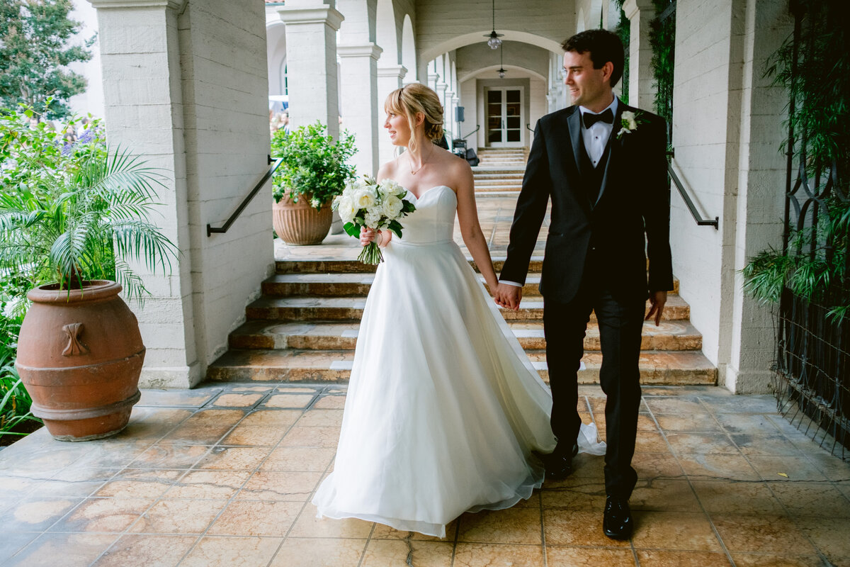 Beautiful bride and groom walk down arch covered walkway on their wedding day