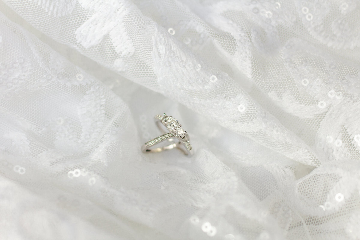 Engagement and wedding ring close up with white wedding dress as backdrop in Tampa, Florida