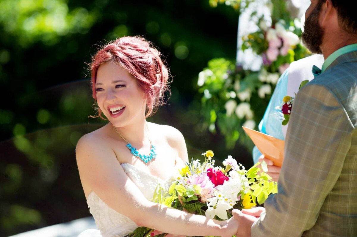 a pretty bride with red hair laughs at the guests during the wedding vows