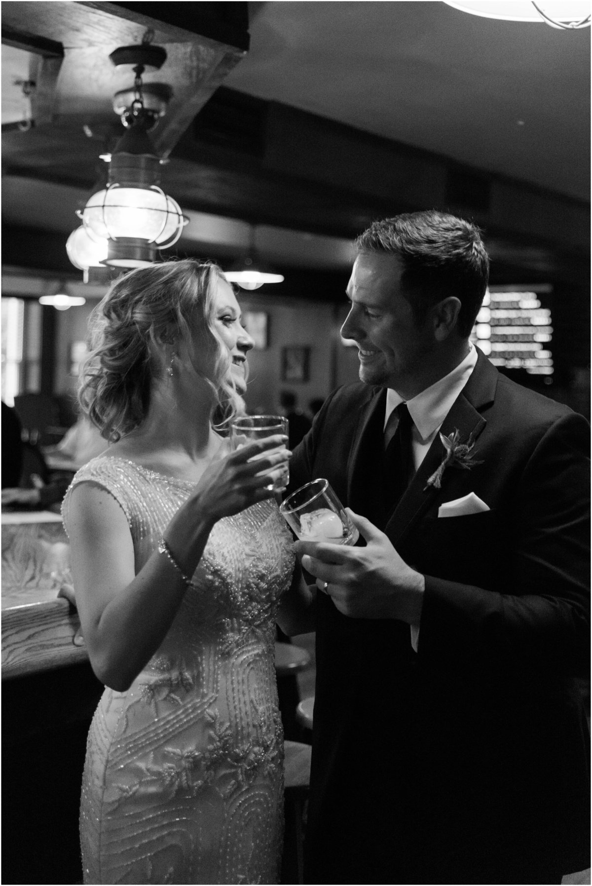Bride and groom toasting by bar, black and white wedding photography