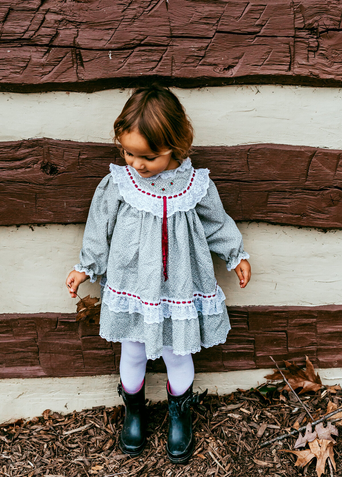 Little girl in front of log cabin
