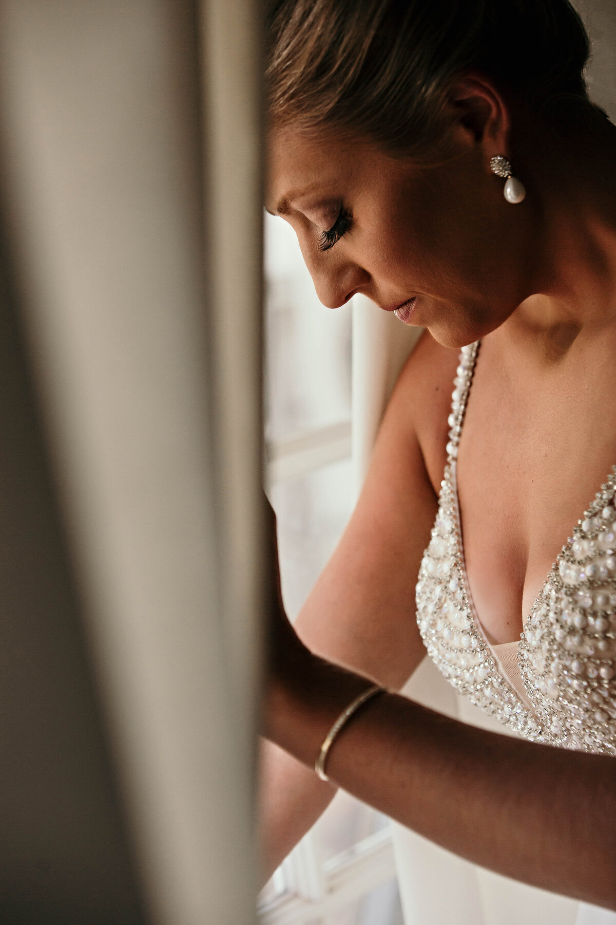 A photograph of the bride all ready for the wedding ceremony, pausing in a quiet moment as she stands by a window, looking down as the sunlight shows off her makeup and beaded dress bodice by Garry & Stacy Photography Co - Sarasota wedding photographer