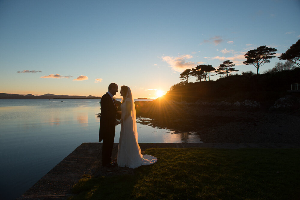 silhouette of bride and groom standing on the edge of a pier at the Parknasilla Hotel, Kenmare with the sun setting in the background