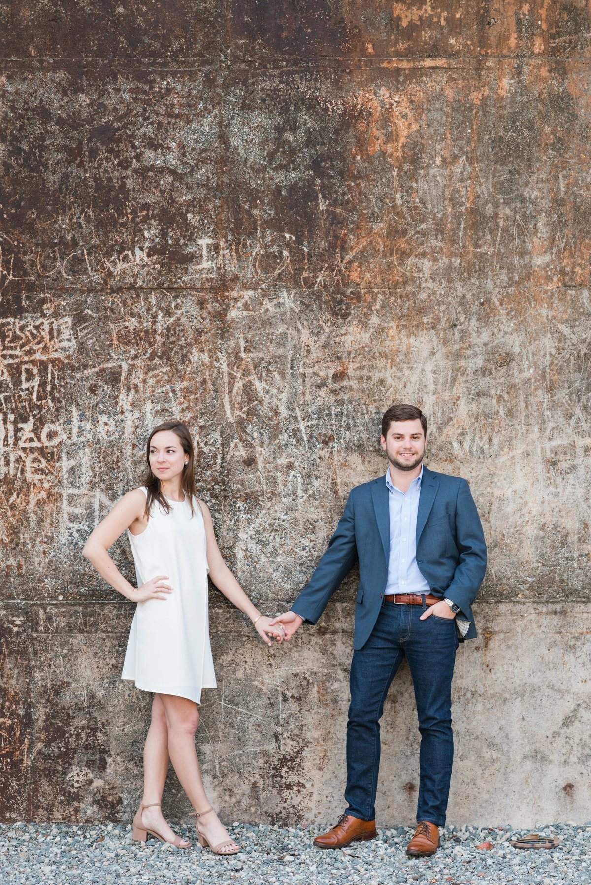 a bride wearing a white dress holding hands with her fiance wearing a navy suit standing in front of an industrial wall in Saxapahaw NC