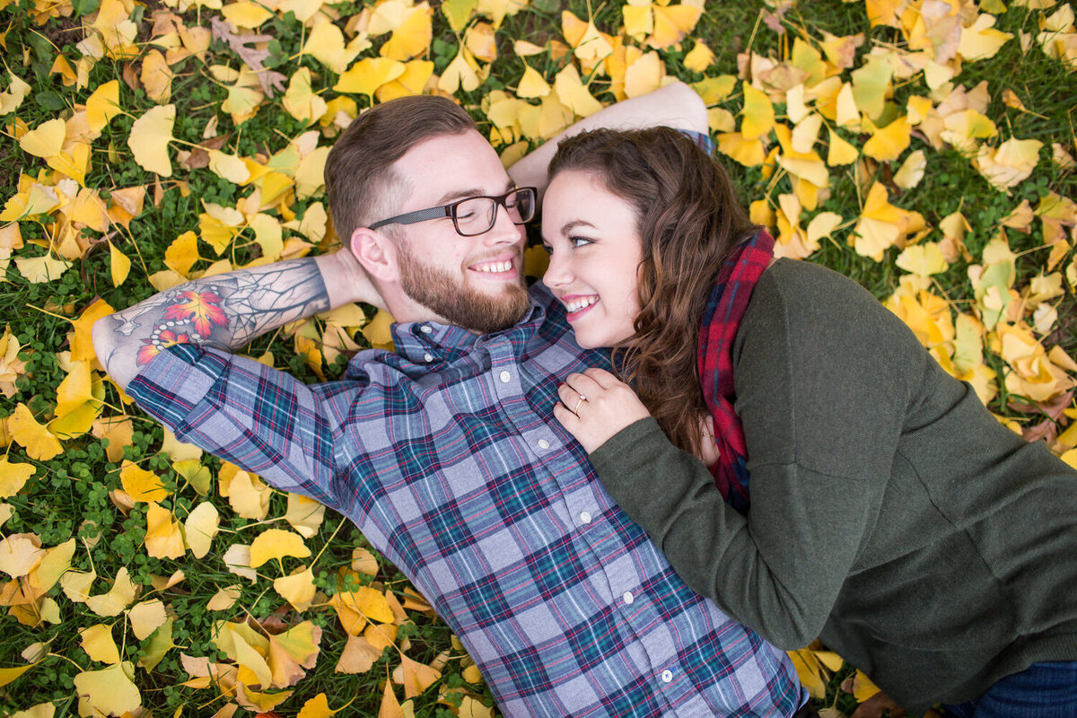 hipster couple laying in fall leaves
