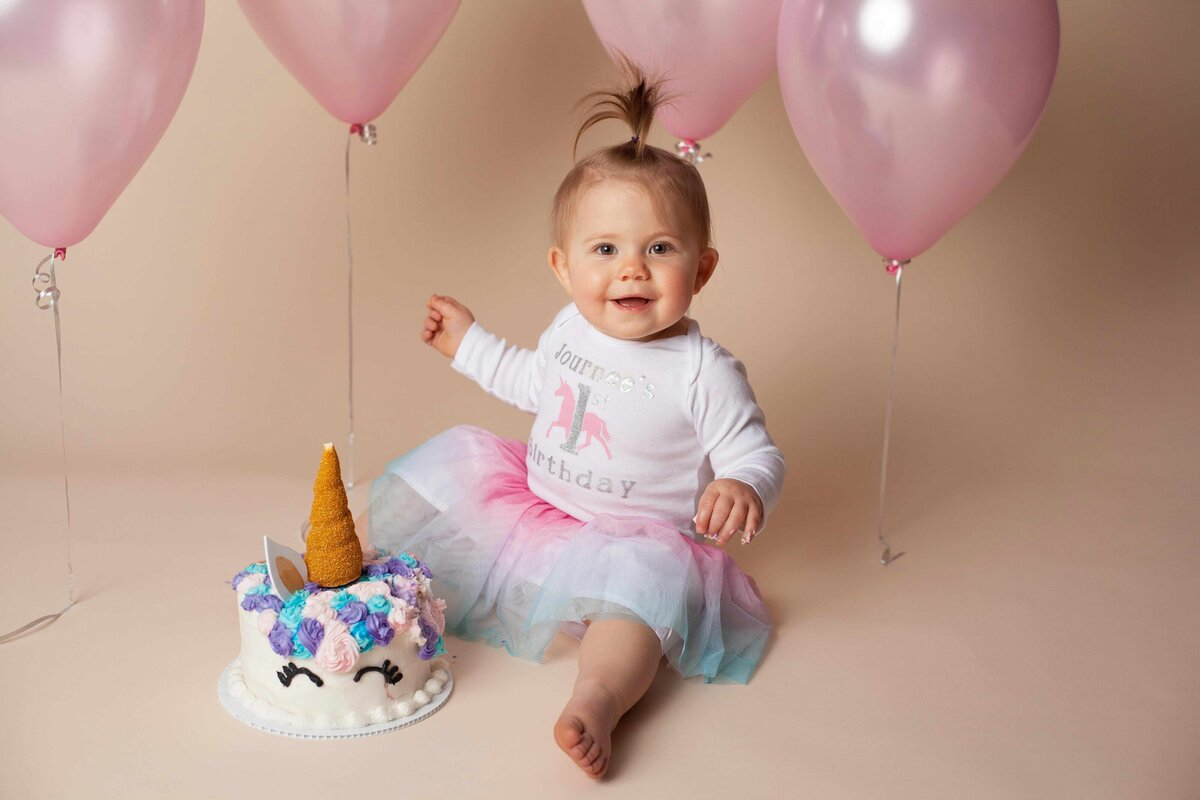 1 year old cake smash session unicorn theme and pink ballons
