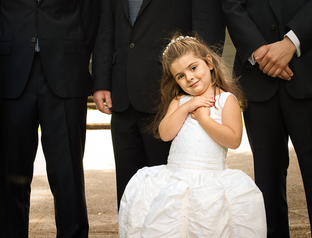 flower girl in princess style dress posing in front of groomsmen