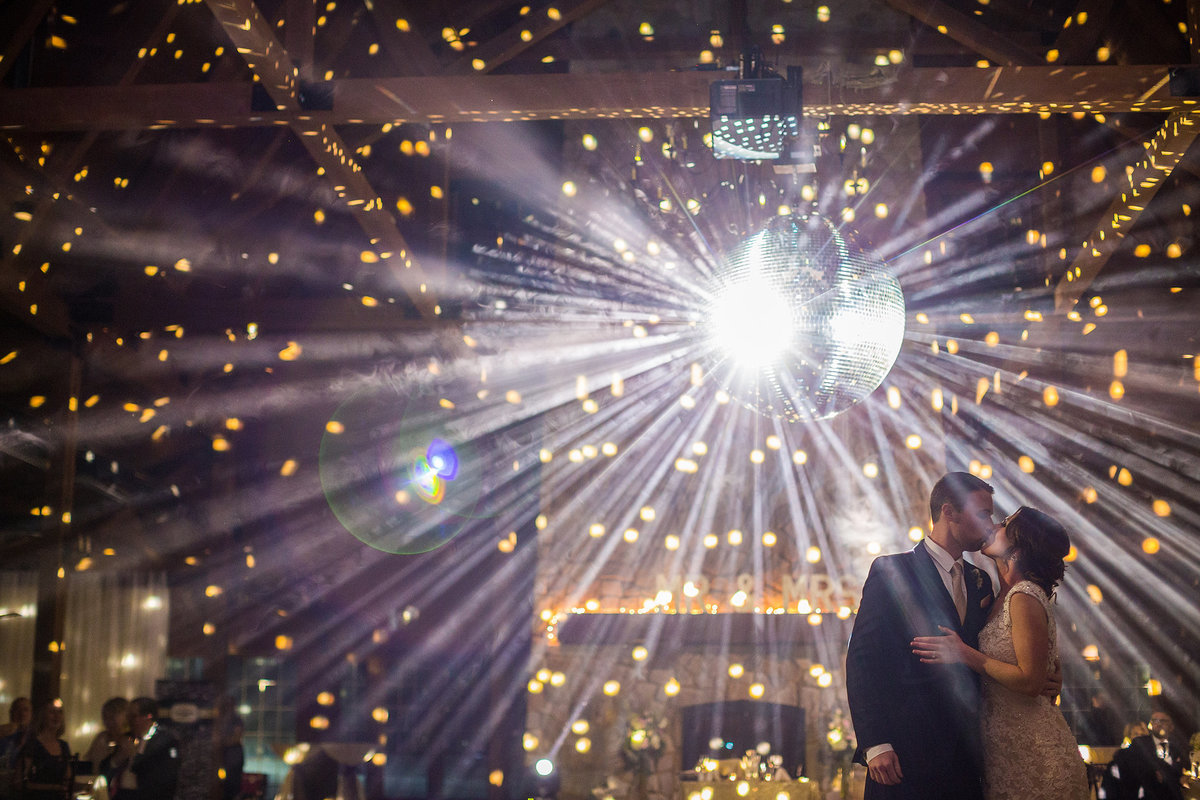 Bride and groom sharing first dance under lights