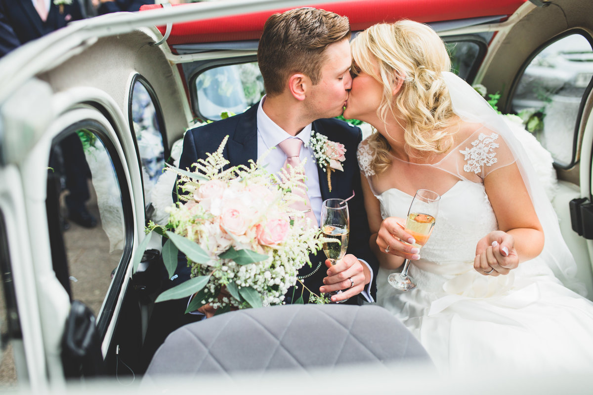 couple kissing in a citroen 2cv convertible after the wedding ceremony
