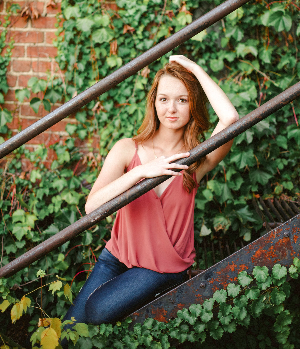 senior girl sits on rusted staircase outside building of ivy and brick