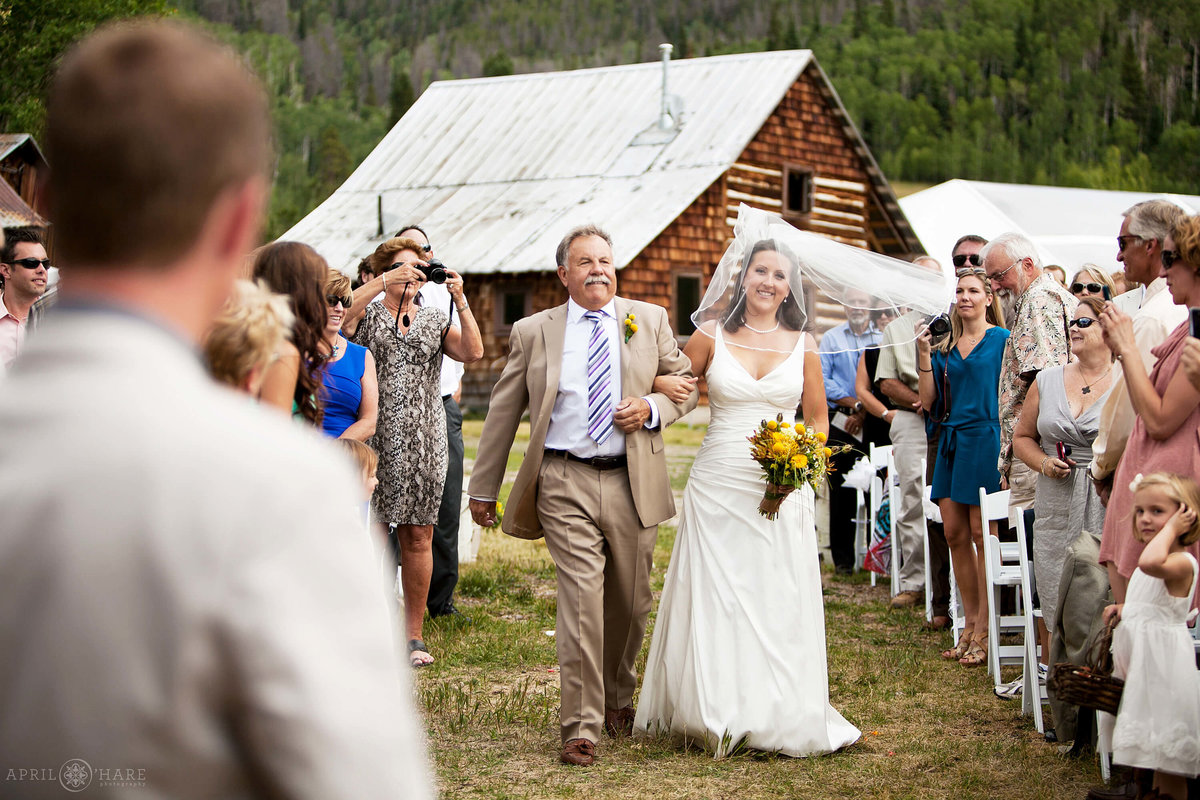Bride walks down the aisle with her dad at Catamount Ranch barn in Steamboat Springs