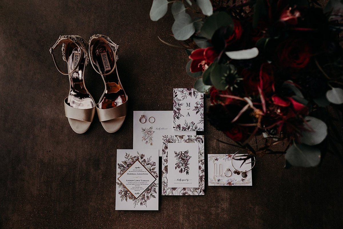 Bride's flowers, invitation, and shoes styled on the floor at t he Paseo